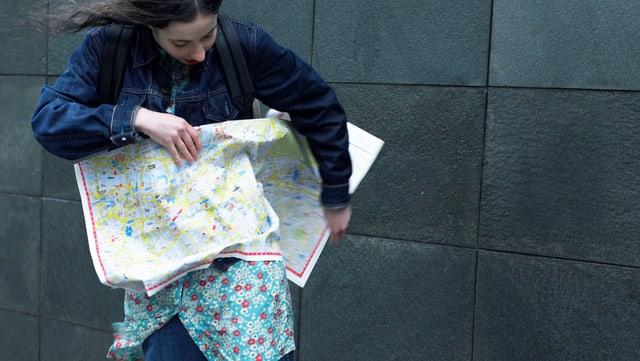 Eine junge Frau hält eine Stadtkarte in den Händen, die vom Wind an ihren Körper geweht wird.