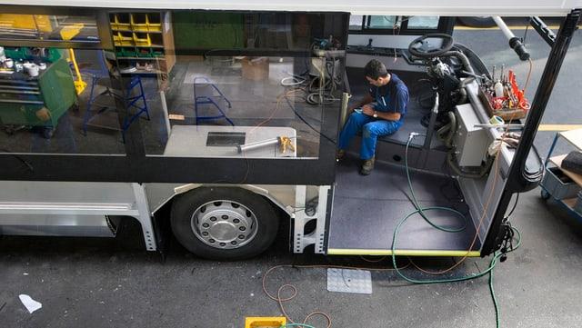 Arbeiter arbeitet an einem halbfertigen Bus