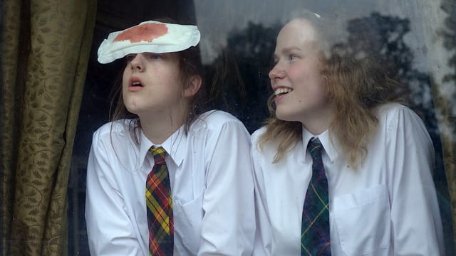 Zwei Mädchen in Schuluniform stehen an einem Fenster, einer klebt eine blutige Binde auf der Stirn.