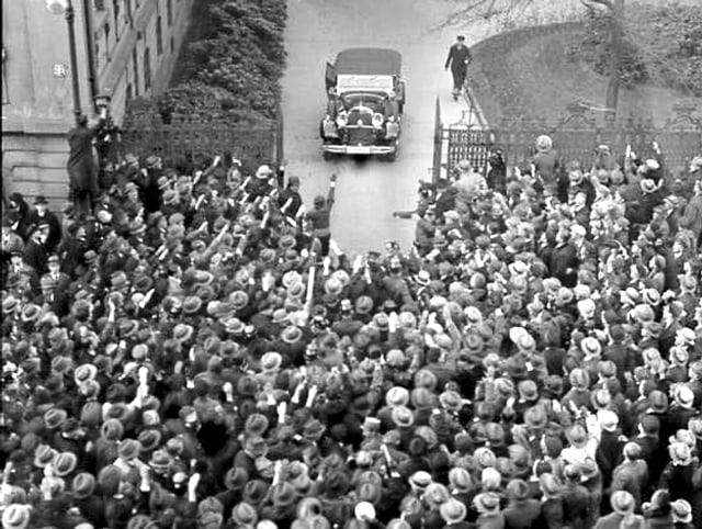 Eine grosse Menschenmenge wartet vor einem Tor auf ein Auto.
