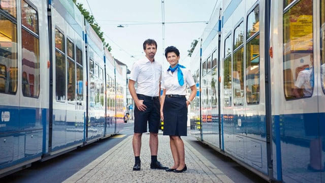 Eine Trampilotin und ein Trampilot  in blauem Jupe und kurzen Hosen, mit weisser Blue und Hemd, zwischen zwei Tram.