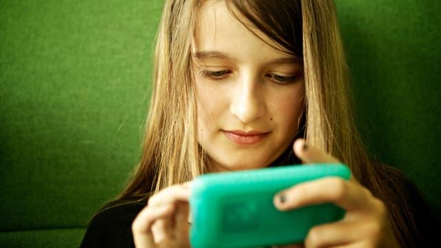 Ein Mädchen schaut in einen iPod Touch.