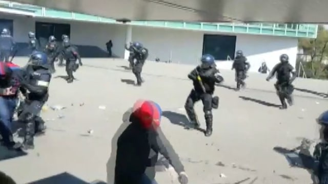 Polizisten und Chaoten auf Plattform