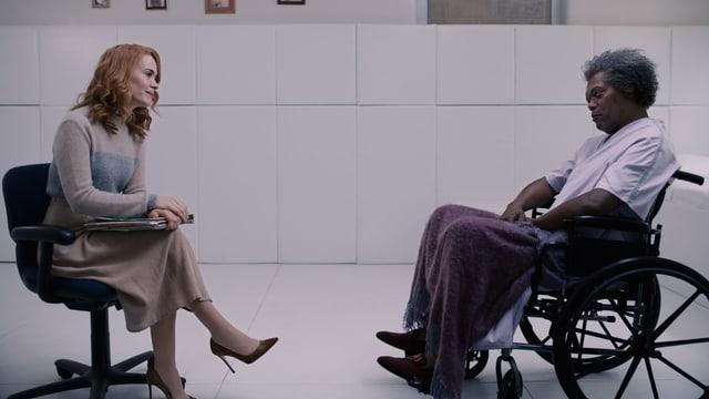Elijah sitzt im Rollstuhl. Eine Therapeutin redet auf ihn ein.