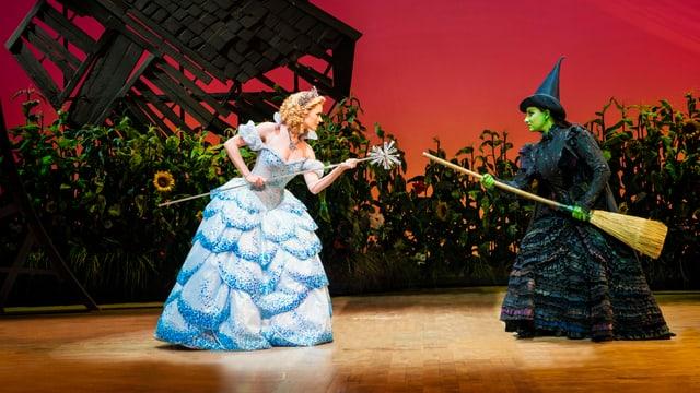 Zwei Schauspielerinnen auf Bühne mit Besen und Zauberstab