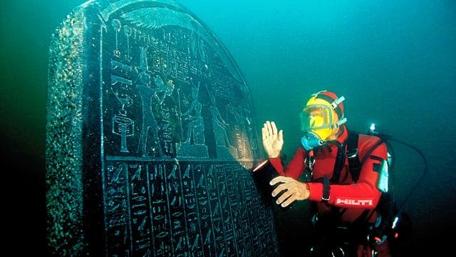 Taucher vor der antiken Stele.