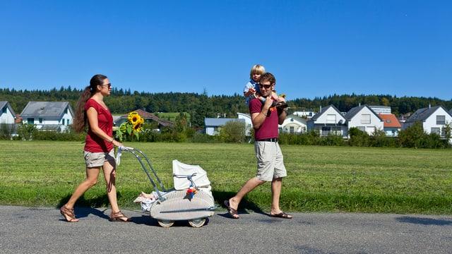 Mutter, Vater und zwei Kinder beim Spazieren vor grüner Wiese und unter blauem Himmel.
