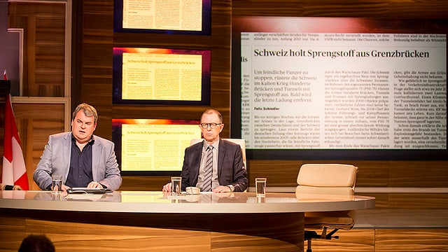 Viktor und Mike am Tisch. Im Hintergrund die Schlagzeile: «Schweiz holt Sprengstoff aus Grenzbrücken».