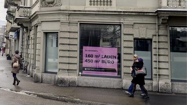 Ein leerstehendes Ladenlokal in Zürich, ein Rosa Vermietungsschild weist auf die freistehende Fläche hin.