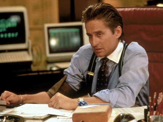 Ein Banker mit Hemd und Hosenträger sitzt an seinem Schreibtisch und schaut kritisch einem Kunden ins Auge.