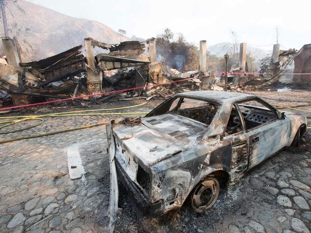 Zerstörtes Auto, im Hintergrund niedergebrannte Gebäude