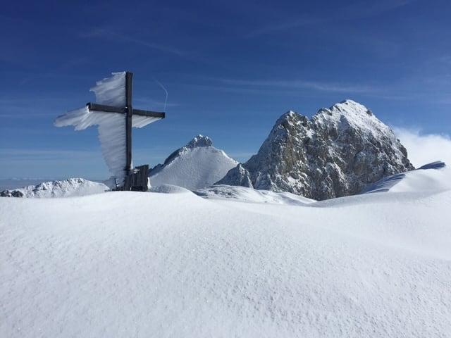 Am Gipfelkreuz hängt eine mächtige Rauheisschicht, es liegt viel Schnee, der Himmel ist blau.
