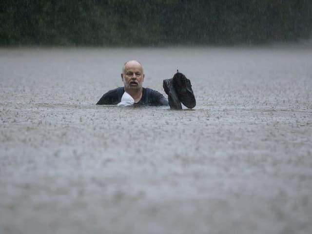 Ein Mann rettet sich uns seine Schuhe aus den Fluten.