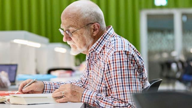 Ein Mann sitzt an einem Tisch und liest in einem Buch.