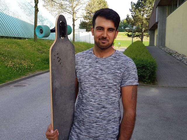 Omid hält sein Longboard in der Hand.