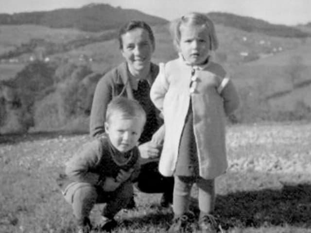 Mutter mit zwei Kleinkindern auf Wiese.
