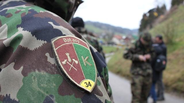 Mann mit Armeeabzeichen steht im Vordergrund. Im Hintergrund Armeeangehörige am Arbeiten.