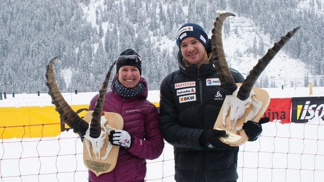 Claudia Schmid e Dario Cologna cun lur trofeas da capricorn.