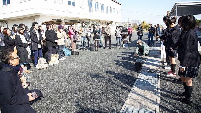 Zuschauer bilden sich in einem Halbkreis auf einer Strasse um Theaterschaffende.