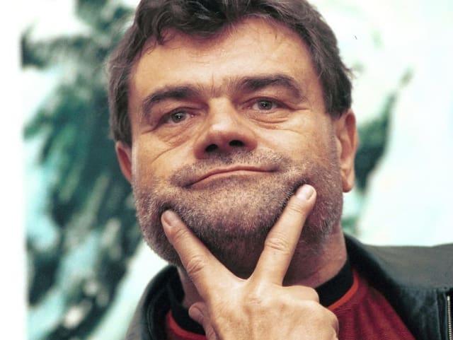 Mann deutet mit Fingern ein Lächeln auf seinem Gesicht an.