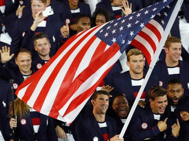 Michael Phelps trägt die US-Flagge ins Stadion.