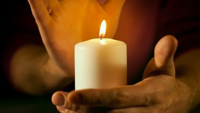 Eine Hand umfasst eine brennende Kerze.