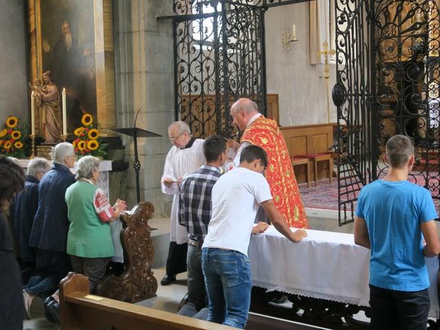 Junge und alte Menschen in einer Kirche.