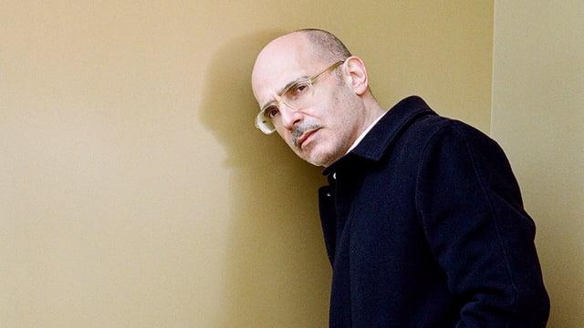 Ein Mann im Mantel mit Glatze und Brille lehnt gegen eine Wand.
