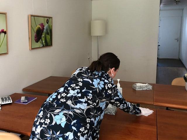 Eine Frau reinigt einen Holztisch.