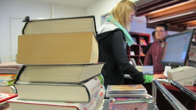 Im Vordergrund ein augestappelte Bücher. Im Hintergrund bedient eine Frau an eine Theke.