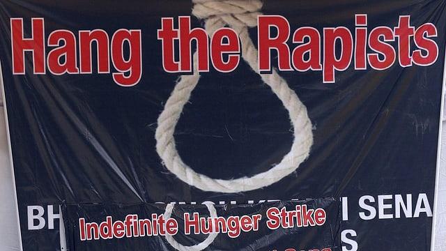 Ein Plakat mit der Aufschrift «Hang the Rapists» und einer Galgenschlaufe.