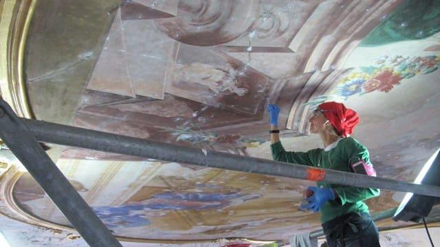 Eine Frau mit rotem Kopftuch und blauen Handschuhen arbeitet an einer Freske.