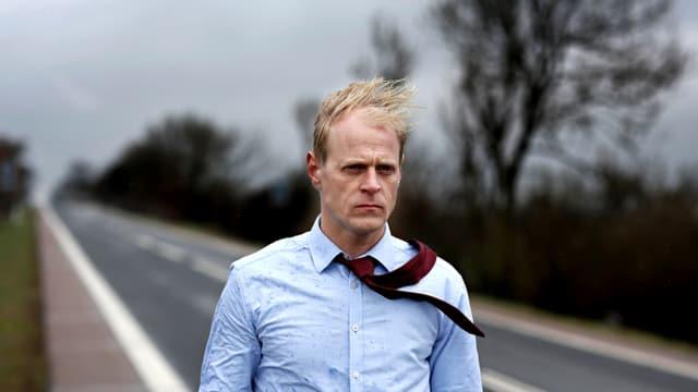 Ein Mann mit verwindetem Haar und Kravatte geht einer Strasse entlang.