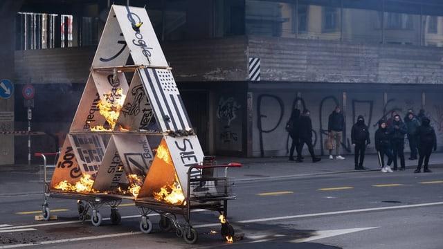 Demonstrants ardan ina chasa da cartas durant la demonstraziun.
