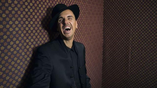 Seven lehnt sich an eine Wand und lacht herzlich. Er ist schwarz angezogen und trägt einen Hut.