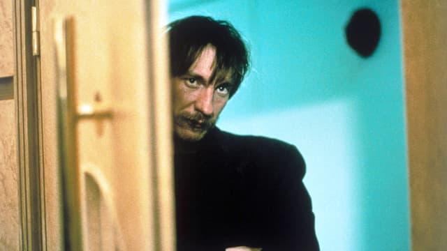 Ein Mann mit finsterem Blick schaut zur Tür rein.