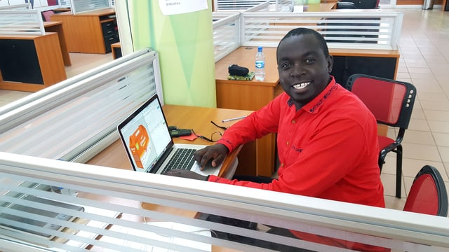 Ein Mann sitzt lächelnd an einem Schreibtisch mit Laptop.