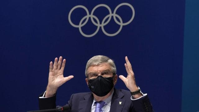Bach trägt eine Hygienemaske und hält beide Hände gestikulierend über den Kopf.