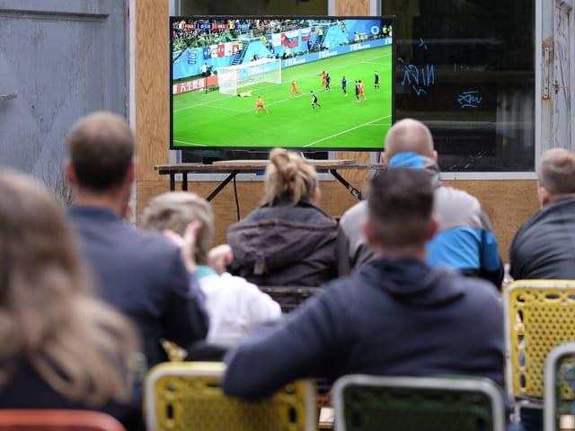 Leute schauen einen Fussball-Match im Fernseher.