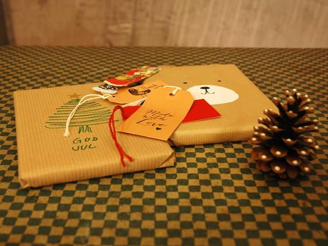 In Packpapier eingepackte Bücher, eines ist mit einem Tannenbaum verziert, das andere mit einem aufgeklebten Bär.