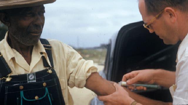 Links im Bild ein schwarzer Mann, rechts ein weisser Arzt, der ihm mit einer Spritze Blut abnimmt.