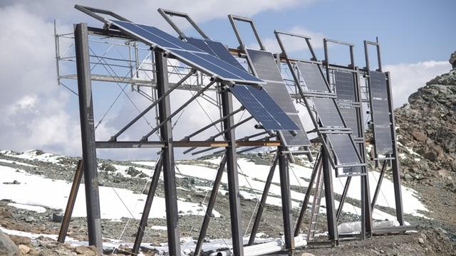 Gestell mit sechs schräg gestellten Solarpanels auf Geröll und Schnee