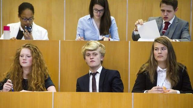 Sechs Jugendliche hören einem Redner zu.