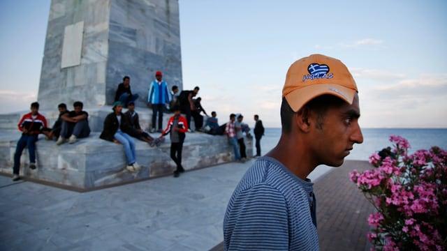 Migrants en il port da Mytilini sin l'insla greca Lesbos guardan suenter ad in bastiment che parta.