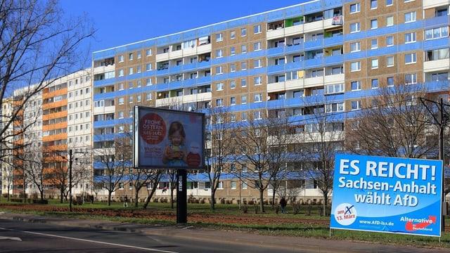 Plattenbau mit einem Wahlplakat der AfD davor.