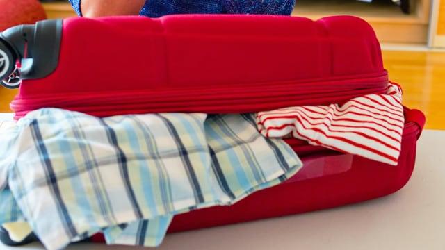 Koffer mit raushängenden Kleidern