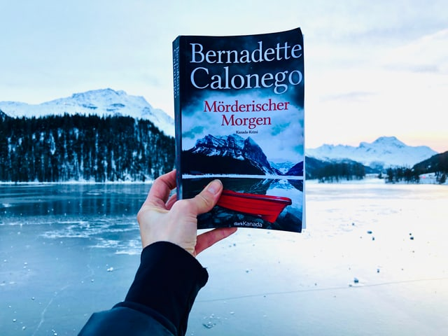 Der Krimi «Mörderischer Morgen» von Bernadette Calonego erscheint vor einem Hintergrund, der mit dem Buchcover harmoniert. Darauf zu sehen: ein See, im Hintergrund Berg, Schnee und Wald.