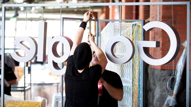 Das Logo von Google wird während der Aufbauarbeiten der re:publica in Berlin an einem Stand angebracht.