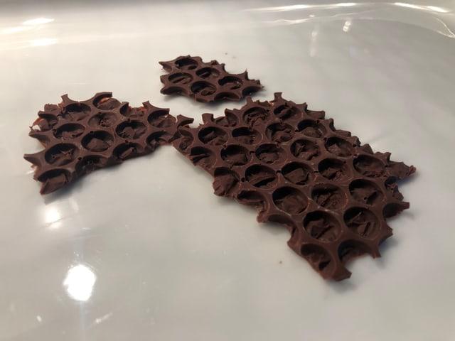Auf einem Teller liegen Schokoladen-Plättchen, die einer Bienenwabe gleichen.