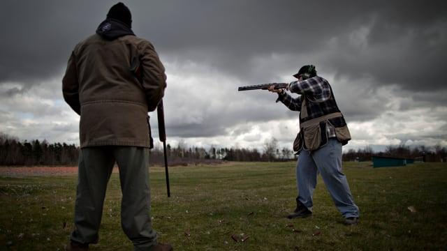 Zwei Jäger schiessen im offenen Feld, am Himmel schwarze Wolken.
